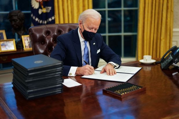 President Biden signs an executive order in the Oval Office, Jan. 20.
